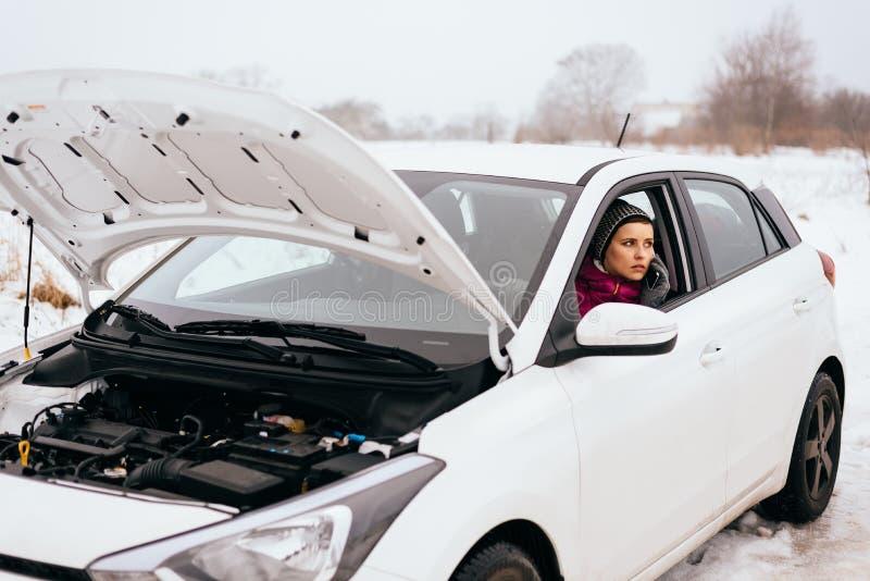 Ajuda da mulher ou auxílio de espera - divisão do carro do inverno fotos de stock royalty free