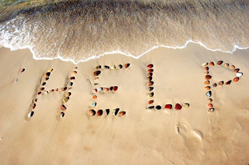 AJUDA da palavra na areia da praia imagem de stock