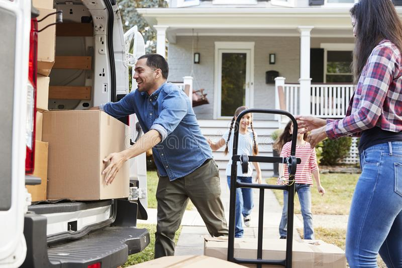 A ajuda das crianças descarrega caixas do dia de Van On Family Moving In imagem de stock royalty free