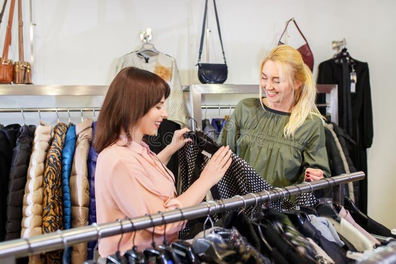 A ajuda do assistente de loja escolhe a roupa fotos de stock royalty free