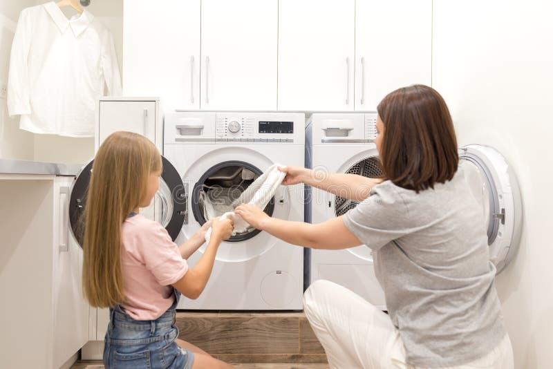Ajudante da mãe e da filha na lavandaria perto da máquina de lavar e do secador que retiram a roupa limpa imagens de stock