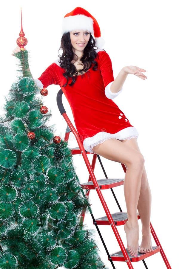Ajudante de Santa da mulher que decora a árvore da pele imagem de stock