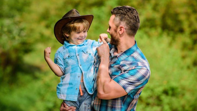 Ajudante pequeno no jardim Rapaz pequeno e pai no fundo da natureza Esp?rito de aventuras Forte como o pai pot?ncia fotos de stock royalty free