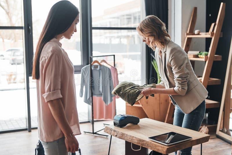 ajudar Jovem mulher bonita que dobra uma camisa para seu custume foto de stock