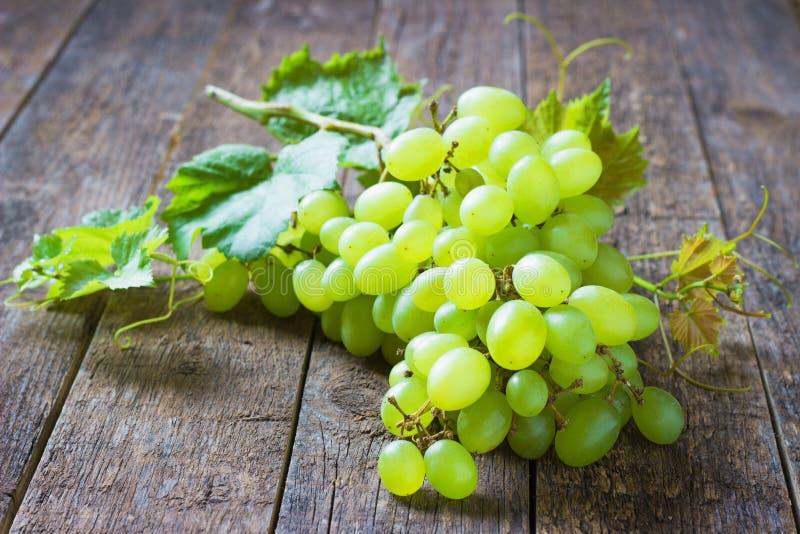 Ajunte uvas verdes no close up de madeira do alimento do fundo fotos de stock royalty free