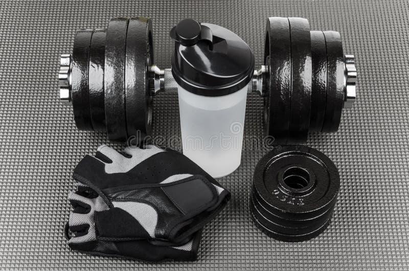Ajustable哑铃、训练手套和振动器在席子 免版税图库摄影