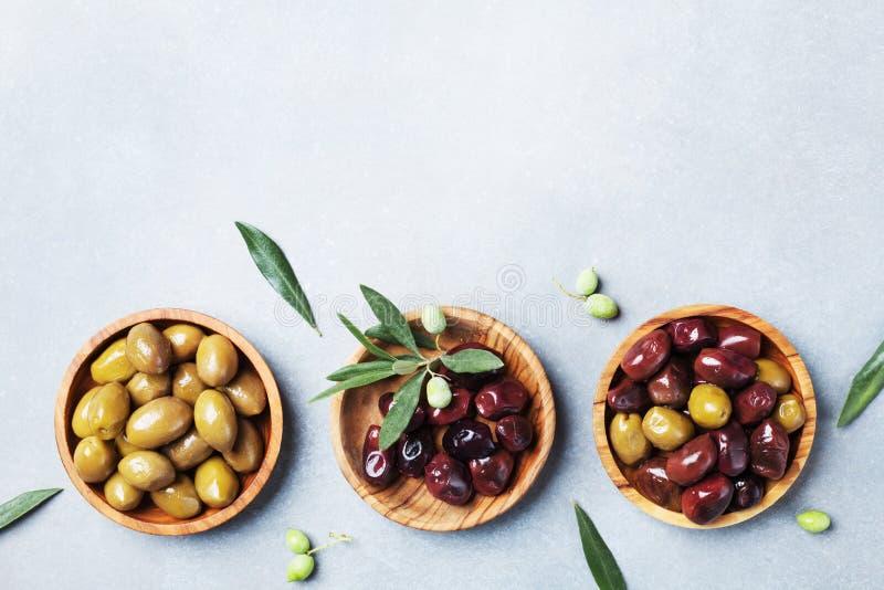 Ajustado das azeitonas em umas bacias de madeira decorou com opinião superior fresca de ramo de oliveira fotografia de stock