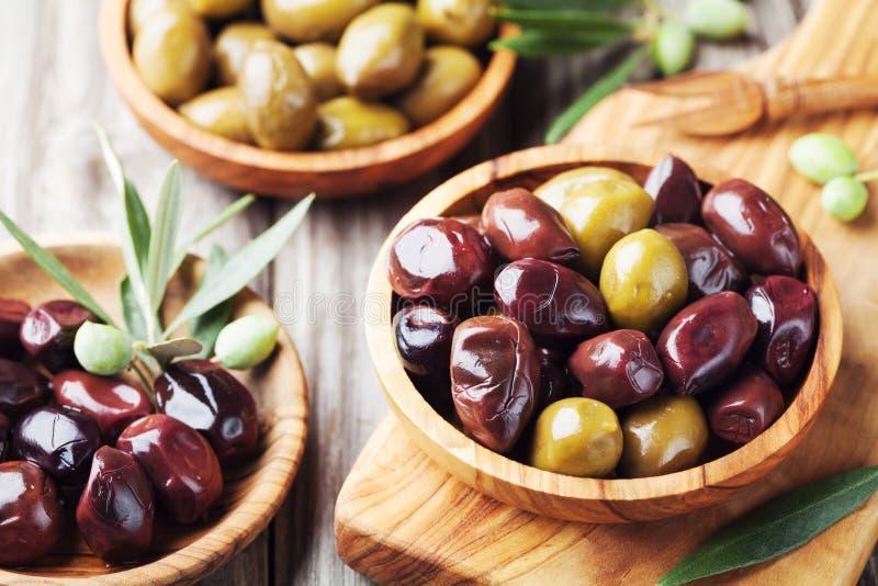 Ajustado das azeitonas em umas bacias de madeira decorou com ramo de oliveira fresco fotos de stock