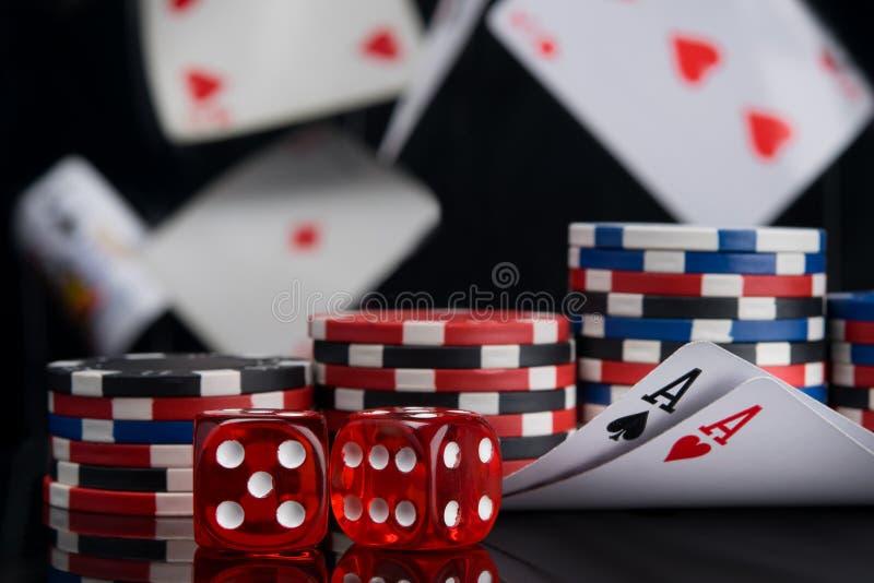 Ajustado para jogar para o dinheiro, os dois ás e os dados em um fundo preto, cartões do voo imagens de stock