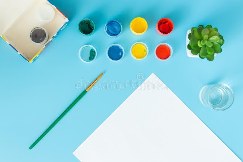 Ajustado para pintar pinta a folha de papel branca com planta carnuda verde, pinturas multicoloridos e escova em um fundo azul co fotos de stock royalty free