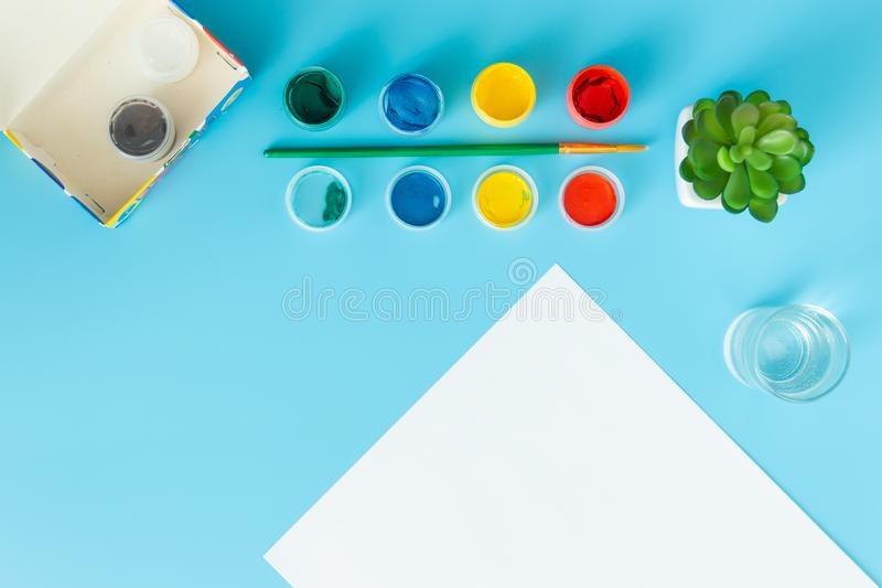Ajustado para pintar pinta a folha de papel branca com planta carnuda verde, pinturas multicoloridos e escova em um fundo azul co foto de stock royalty free