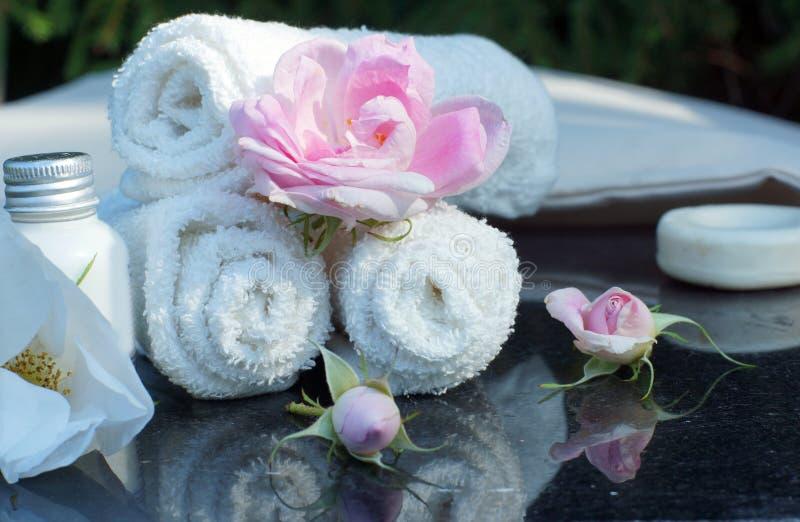 Ajustado para tratamentos exteriores dos termas, toalhas brancas dobradas, sabão, loção e flores perfumadas imagens de stock