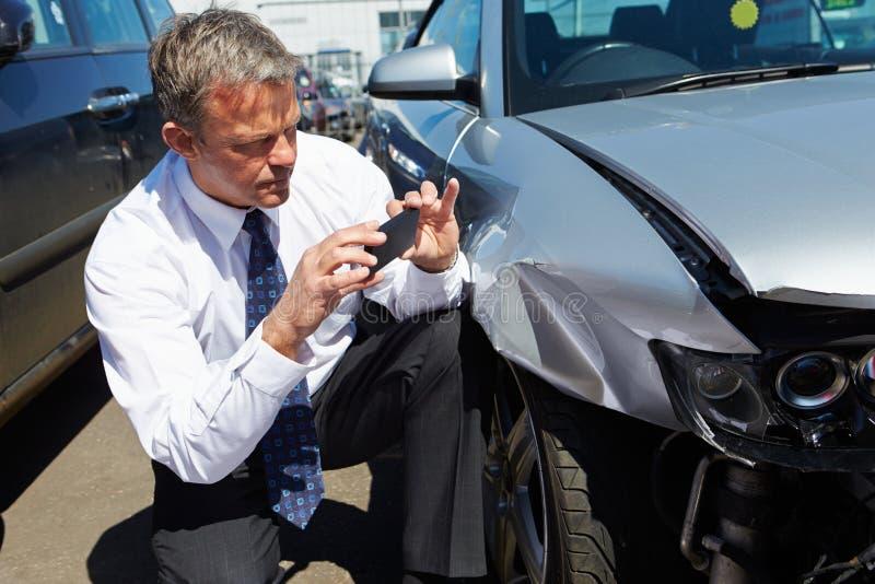 Ajustador de pérdida que examina el coche implicado en accidente imagenes de archivo
