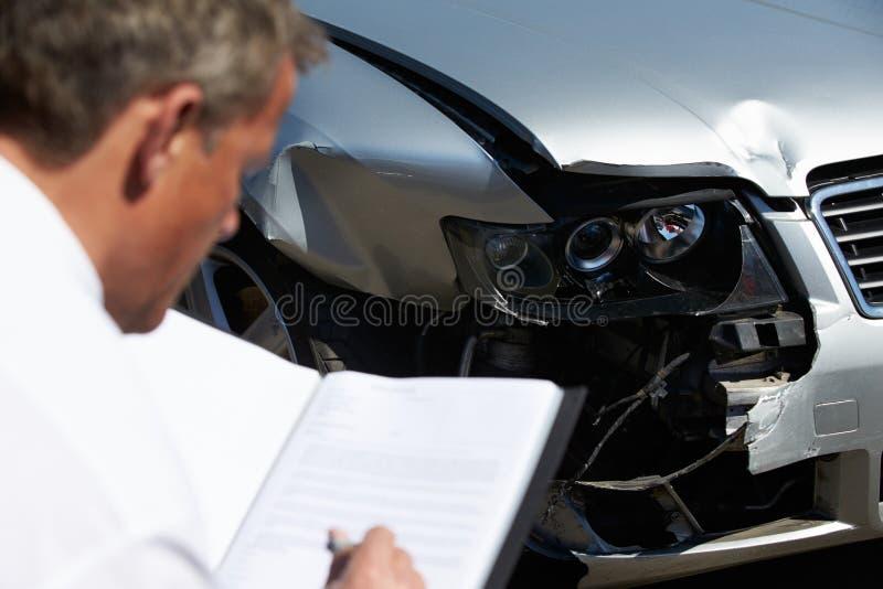 Ajustador de perda que inspeciona o carro envolvido no acidente foto de stock