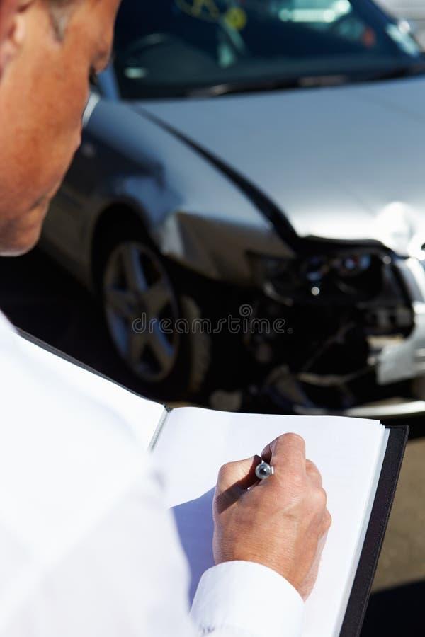 Ajustador de perda que inspeciona o carro envolvido no acidente foto de stock royalty free