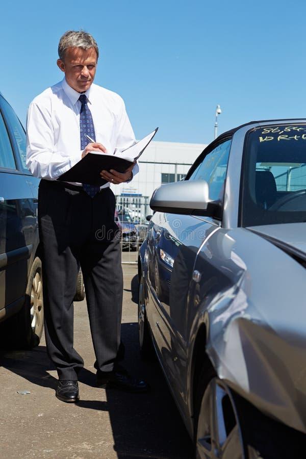 Ajustador de perda que inspeciona o carro envolvido no acidente fotografia de stock
