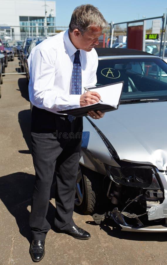 Ajustador de perda que inspeciona o carro envolvido no acidente imagem de stock royalty free