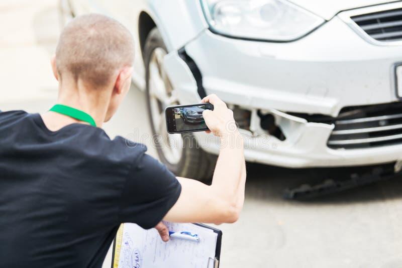 Ajustador do agente de seguros ou de perda que inspeciona o automóvel danificado foto de stock