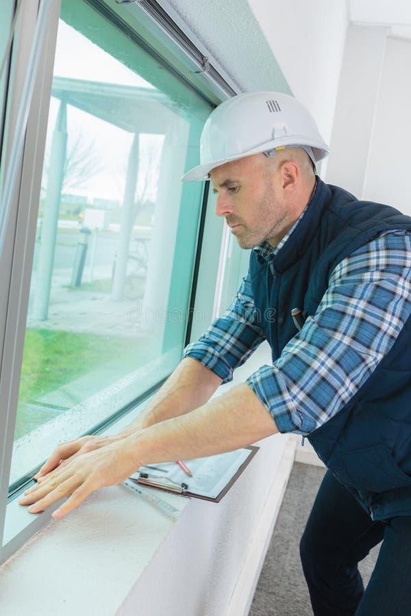 Ajustador masculino de la ventana que trabaja dentro imagen de archivo libre de regalías