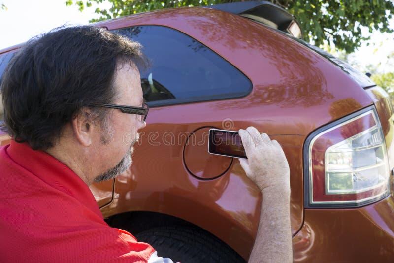 Ajustador que toma fotos de dano ao veículo foto de stock