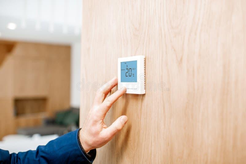 Ajustando a temperatura com termostato em casa fotografia de stock royalty free