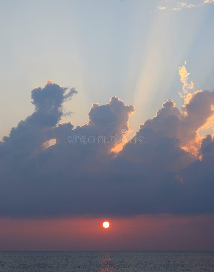Ajuste amarelo dourado de Sun sobre o oceano com os raios crepusculares que espalham no céu azul das nuvens escuras - Skyscape foto de stock royalty free