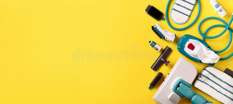 Ajuste com os líquidos de limpeza profissionais modernos do vapor no fundo amarelo Vista superior, configuração lisa Bandeira com imagem de stock