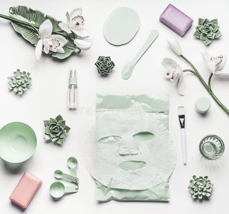 Ajuste cosmético verde del cuidado de piel con las flores de la orquídea, los accesorios y la máscara facial de la hoja que calma foto de archivo libre de regalías