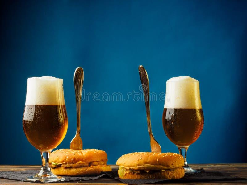 Ajuste da cerveja e dos hamburgueres em uma tabela de madeira foto de stock