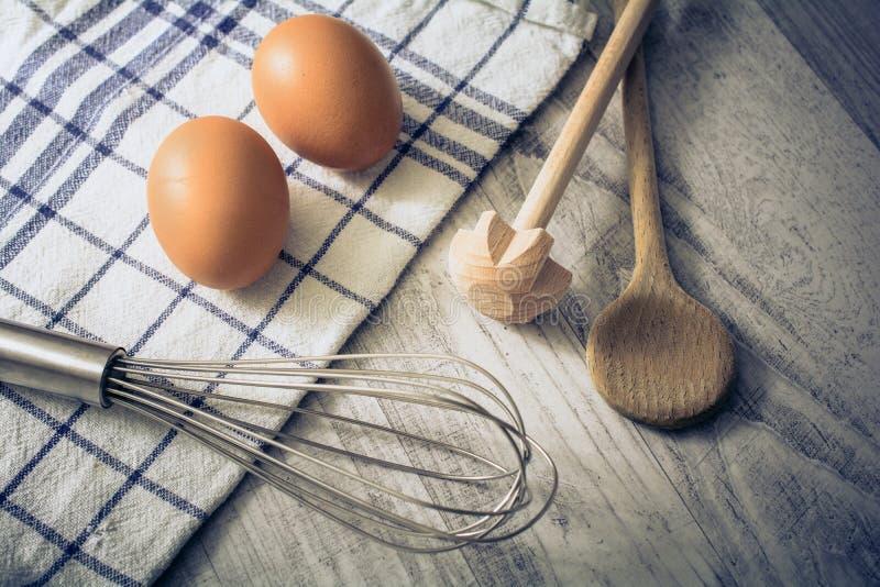 Ajuste da cozinha com 2 ovos, toalha, colher de madeira e Querl e um Eggbeater em uma tabela fotografia de stock