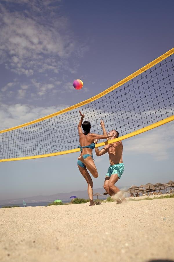 Ajuste da mulher e do homem, forte, saudável, fazendo o esporte na praia Conceito do voleibol de praia Os pares têm o divertiment fotografia de stock