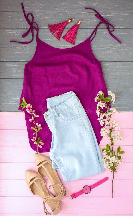 Ajuste da roupa fêmea na moda, dos acessórios e dos ramos de florescência no fundo de madeira, configuração lisa fotografia de stock