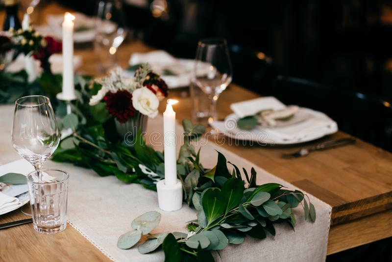 Ajuste da tabela de banquete Placas, forquilhas, velas na tabela de madeira com decoração agradável Vidros da cutelaria e de vinh foto de stock