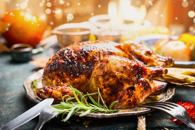 Ajuste da tabela de jantar do dia da ação de graças com o peru ou a galinha roasted inteira na placa com cutelaria, iluminação fe fotografia de stock royalty free