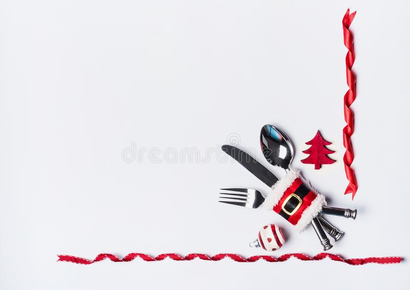 Ajuste da tabela de jantar do Natal com a cutelaria decorada com correia de Santa, árvore de Natal e fitas no fundo branco, vista fotos de stock royalty free