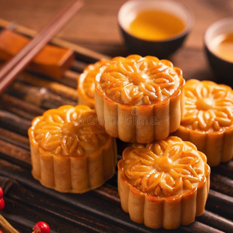 Ajuste da tabela do Mooncake do bolo da lua - o círculo deu forma à pastelaria tradicional chinesa com os copos de chá no fundo d fotografia de stock