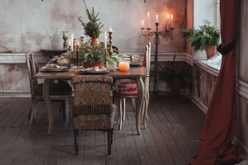 Ajuste da tabela do Natal Cadeiras do vintage, ramos de pinheiro naturais, velas Decorações rurais ou rústicas do estilo imagens de stock
