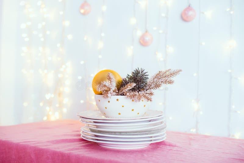 Ajuste da tabela do Natal Não serviu os pratos brancos com decoração e abeto do ouro na toalha de mesa cor-de-rosa com luzes e an imagem de stock