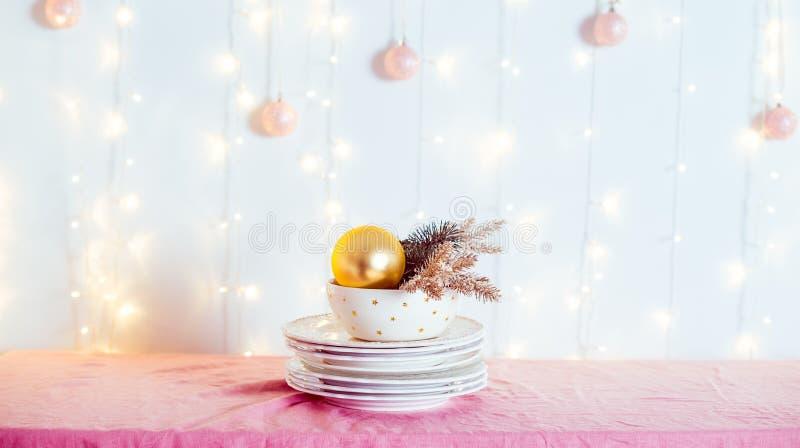 Ajuste da tabela do Natal Não serviu os pratos brancos com decoração e abeto do ouro na toalha de mesa cor-de-rosa com luzes borr imagem de stock royalty free