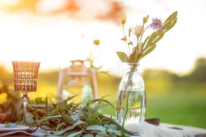 Ajuste da tabela do vintage com a flor no vaso em uma tabela Decoração rústica do casamento do estilo com por do sol no fundo fotografia de stock royalty free