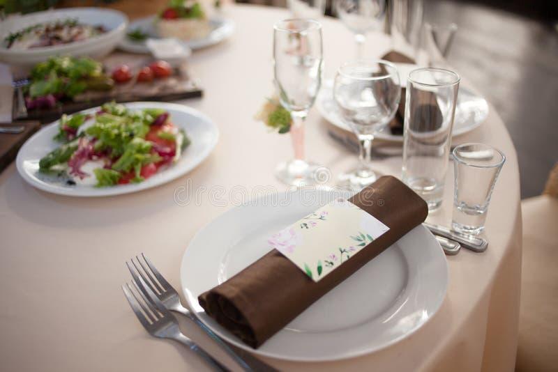 Ajuste da tabela no restaurante Cartão e guardanapo do convidado fotografia de stock royalty free