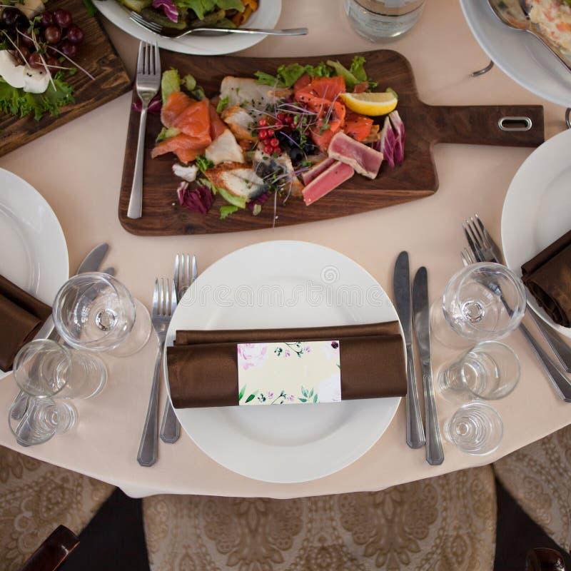 Ajuste da tabela no restaurante Cartão e tapas do convidado foto de stock royalty free