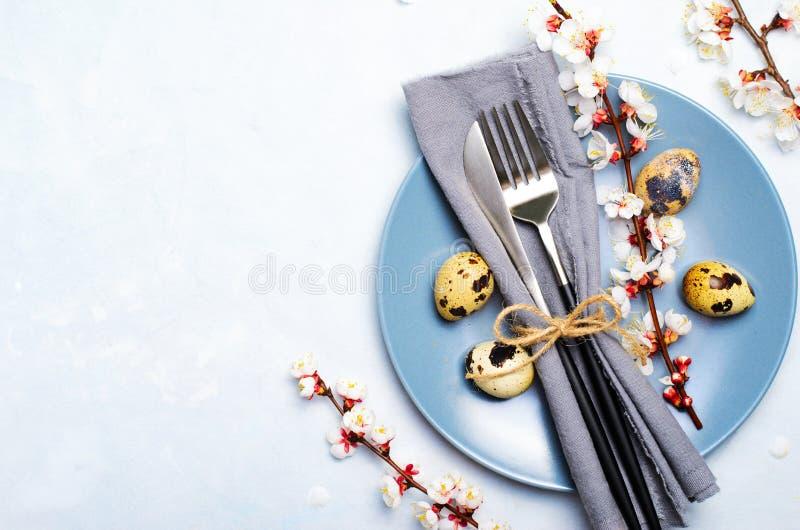 Ajuste da tabela da Páscoa com ovos e ramos de codorniz na flor, fundo dos feriados da mola imagens de stock