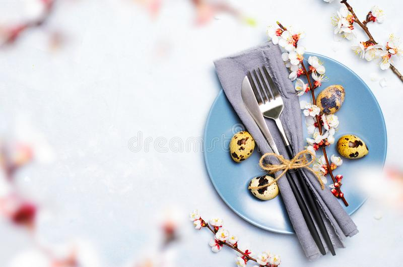 Ajuste da tabela da Páscoa com ovos e ramos de codorniz na flor, fundo dos feriados da mola imagens de stock royalty free