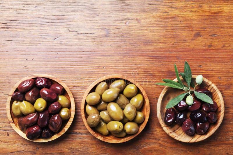 Ajuste das azeitonas em umas bacias de madeira decoradas com opinião superior de ramo de oliveira imagem de stock