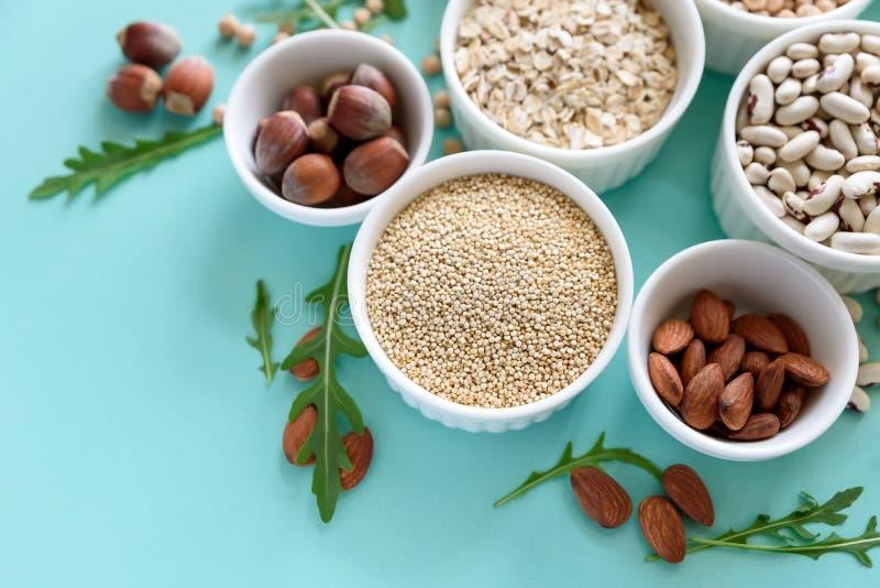 Ajuste das bacias com quinoa, a lentilha, o grão-de-bico, trigo, a noz, a amêndoa, a avelã e sésamo orgânicos Variedade dos cerea foto de stock royalty free