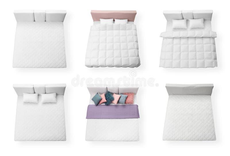 Ajuste das camas modernas com os colchões macios confortáveis no fundo branco imagem de stock