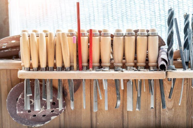 Ajuste das ferramentas e do equipamento do woodworking pendurados na parede na carpintaria Formões, brocas e lápis diferentes na  fotografia de stock
