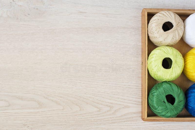 Ajuste das linhas coloridas para fazer malha, fazendo crochê na caixa de madeira na tabela fotografia de stock