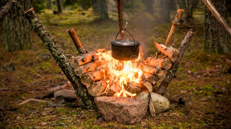 Ajuste de Bushcraft con un pote que acampa que cuelga sobre un fuego ardiente imagenes de archivo